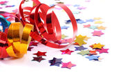 Confetti with streamers on white — Stock Photo