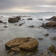 Rocky shoreline with clouds - Stock Photo
