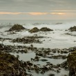 Sunset over waves and rocks - Stock Photo