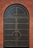 Old heavy metal door in a brick wall — Stock Photo