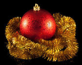Red christmas ball and gold tinsel — Stock Photo