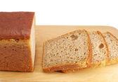 Cut rye bread on wooden board — Stock Photo