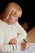 Senior woman filling in an document — Stock Photo