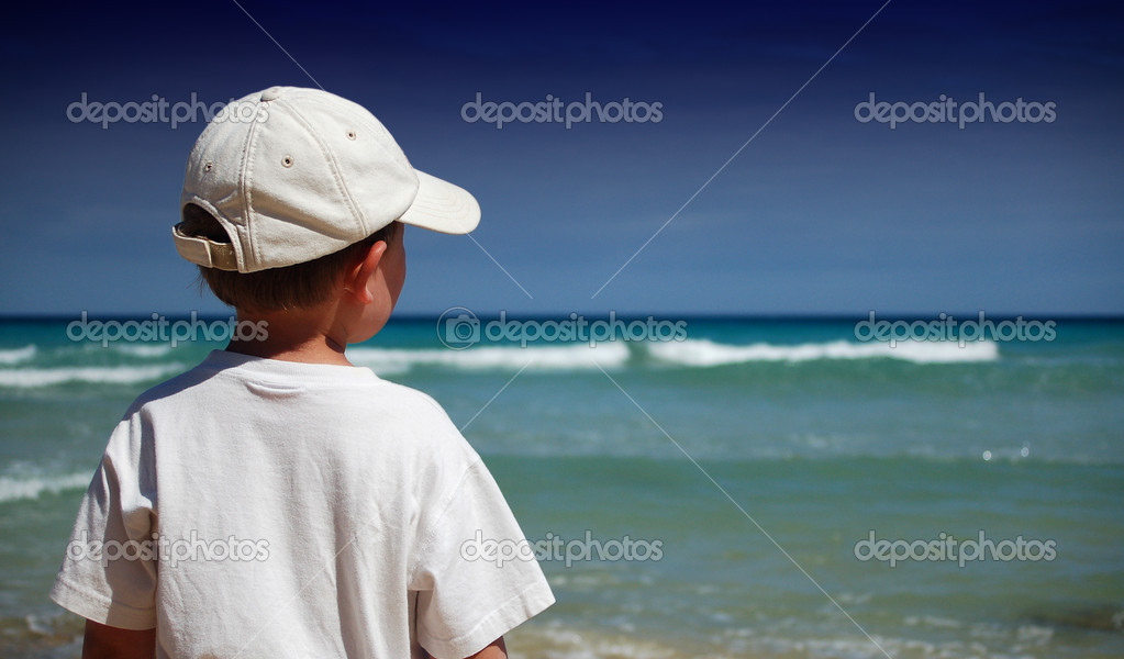 Boy in white shirt watches the waves on the beach — Stock Photo #2175949