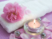 Aromatic candle and petals of rose — Stock Photo