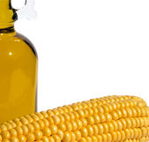 Corn and bottle of oil on a white — Stock Photo