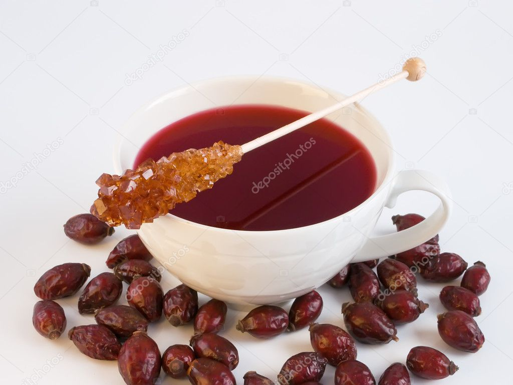 Cup of tea with wild rose hips and sugar sticks close-up — Stock Photo #2516454