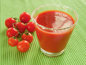 Tomato juice and sprig of cherry — Stock Photo