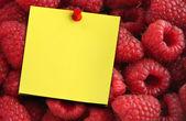 Raspberries and yellow note — Stock Photo