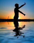 Sunset silhouette doing excercises — Stockfoto