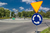 Roundabout with a clock and sign before — Stock Photo