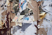 Paper leftovers on an old wooden wall — Stock Photo