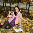 Stock Photo: Funny college girl studying in autumn pa