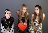 Three happy girls holding red heart — Stock Photo