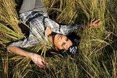Beautiful young woman lying on field — Stock Photo