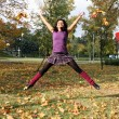 Joyful woman jumping in autumn park - Stock Photo