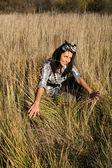 Beautiful young woman sitting on field — Stock Photo