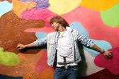 Handsome man standing near graffiti wall — Stock Photo