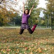 Stock Photo: Joyful woman jumping in autumn park