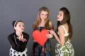 Três meninas felizes segurando coração vermelho — Fotografia Stock