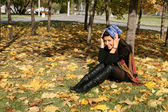 Funny girl with a a book in autumn park — Stock Photo