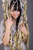 Girl standing among tinsel — Stock Photo