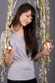 Girl standing among tinsel — Stock Photo