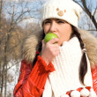 Funny girl eating apple outdoor — Stock Photo
