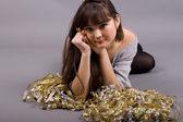 Girl lying among tinsel — Stock Photo