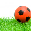 Orange soccer ball on grass — Stock Photo