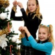 Two girls decorating christmas tree — 图库照片