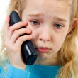 Stock Photo: Sad girl on the phone