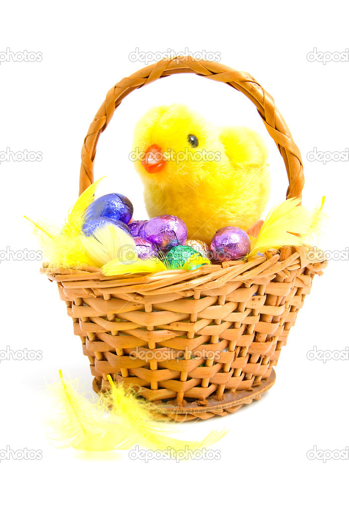 Cane basket with colorful chocolate easter eggs and yellow little chicken over white background — Stock Photo #2270503
