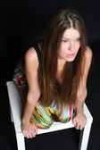Long-haire girl sitting on the chair — Stock Photo
