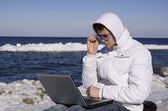 Young man with the computer on seacoats — Stock Photo
