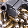 Pistol on pile of bullets — Stock Photo