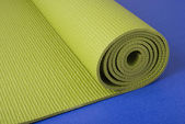 Green yoga mat on blue — Stock Photo