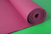 Pink yoga mat on green — Stock Photo