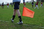 Linesman holding flag in a local football game — Stock Photo