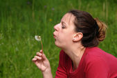 Attractive female blowing a dandelion — Stock Photo