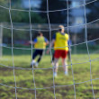 Soccer players in front of net — Stock Photo