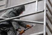 Man washing building facade — Stock Photo