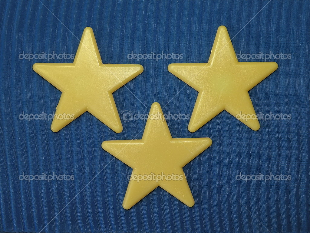 Three yellow stars isolated on blue fabric  Stock Photo #2222256