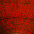 Bamboo cane roof covered with red foil - Stock Photo