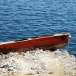 Old red boat stranded on rocks — Stock Photo