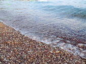 Motion blurred wave on pebble beach — Stock Photo
