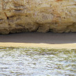 Small sandy beach under rocky cliff - Stock Photo