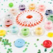 Sewqing bobbins, buttons, beads on white — Stock Photo