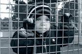Ernstige kind op zoek door hek — Stockfoto