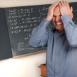 Desperate man in a class with complicated formulae in the blackboard — Stock Photo #2200132